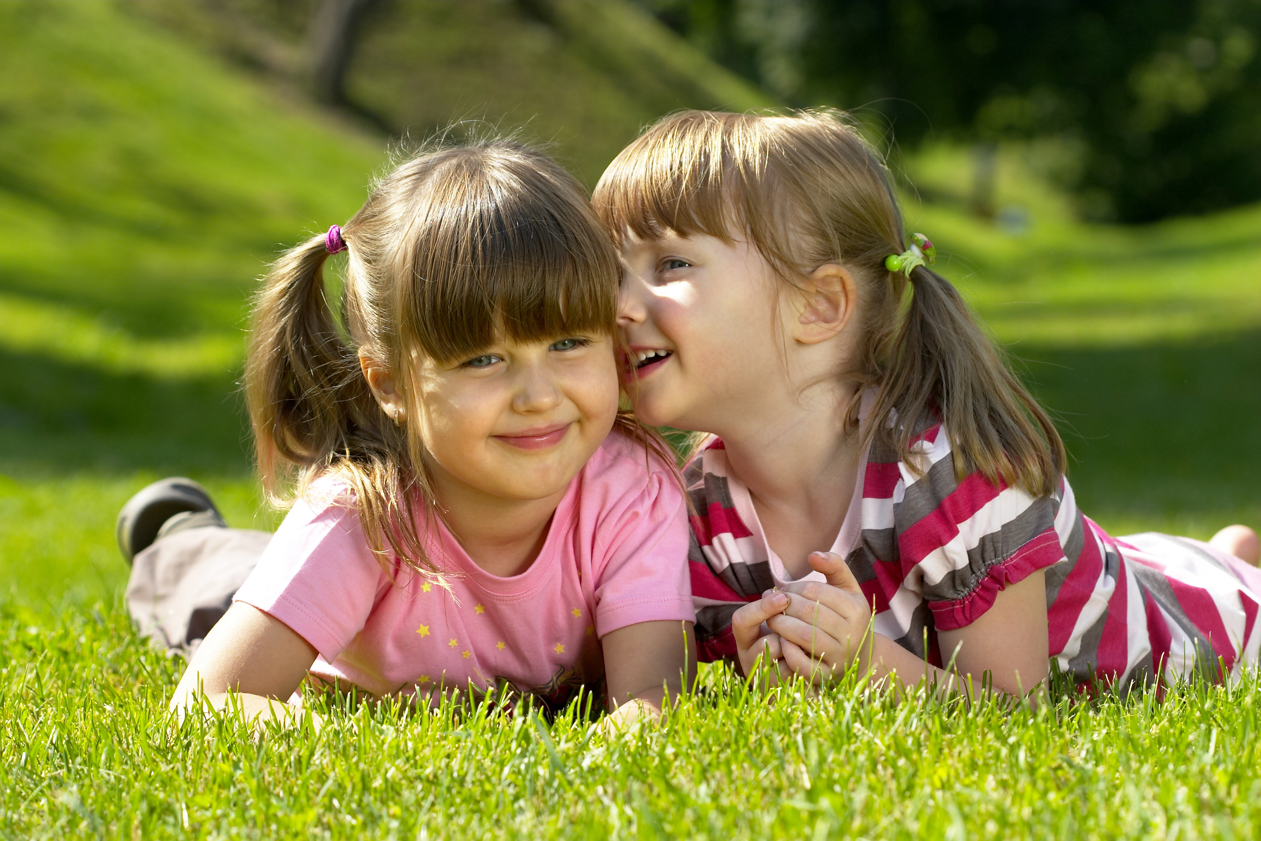 Two little girl lying on the grass in the park. One whispering a secret to another.